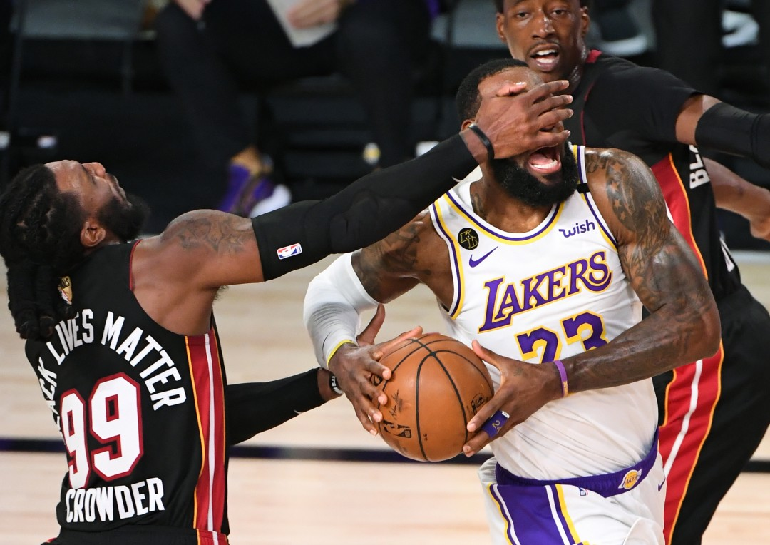 Lakers forward LeBron James is hit in the face by Miami Heat forward Jae Crowder while driving to the basket in Game 6 of the NBA Finals on Sunday.(Wally Skalij / Los Angeles Times)