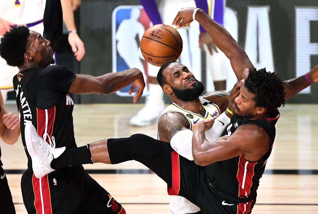 Lakers forward LeBron James is fouled by the Miami Heat's Jimmy Butler, right, while driving to the basket as Bam Adebayo tries to help on defense in the second quarter in Game 6 of the NBA Finals in Orlando Sunday. (Wally Skalij/Los Angeles Times)