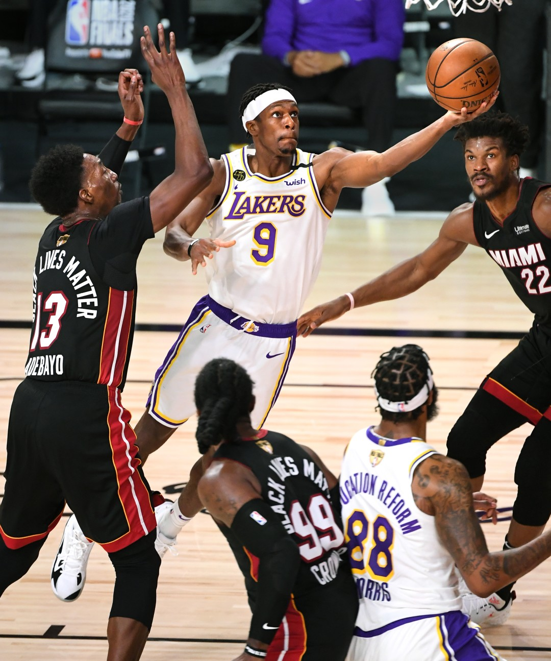 Lakers guard Rajon Rondo scores in front of Miami Heat forwards Bam Adebayo, left, and Jimmy Butler, right, during the second quarter of Game 6 of the NBA Finals on Sunday.(Wally Skalij / Los Angeles Times)